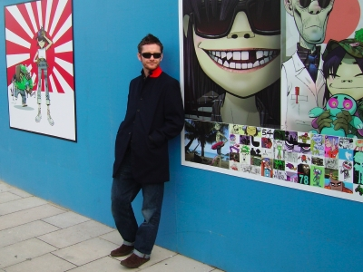 Jamie Hewlett poses with his artwork outside the F