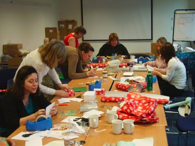 Volunteers wrap gifts donated as part of last year