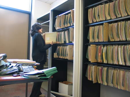 A receptionist helps to organise patient files